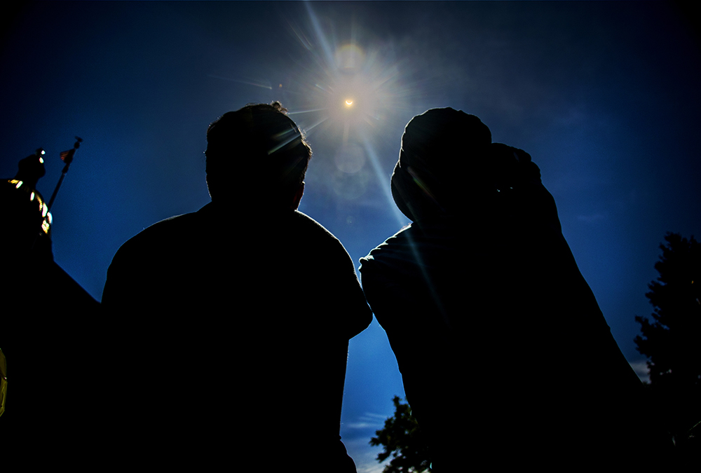 Basma (right) and Niama Al Nima gaze up at a solar eclipse over the Capitol, Aug. 21, 2017. (Kevin J. Beaty/Denverite)solar eclipse; capitol hill; denver; colorado; the sun; kevinjbeaty; denverite;
