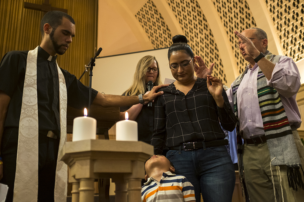 Rev. Nathan Adams (left to right), Rev. Angie Heesacker and Rabbi Adam Morris lay hands on Araceli Velasquez, welcoming her into sanctuary. Aug. 23, 2017. (Kevin J. Beaty/Denverite)  Park Hill United Methodist Church; Temple Micah Synagogue; park hill; sanctuary; immigration; undocumented; denver; colorado; denverite; kevinjbeaty;