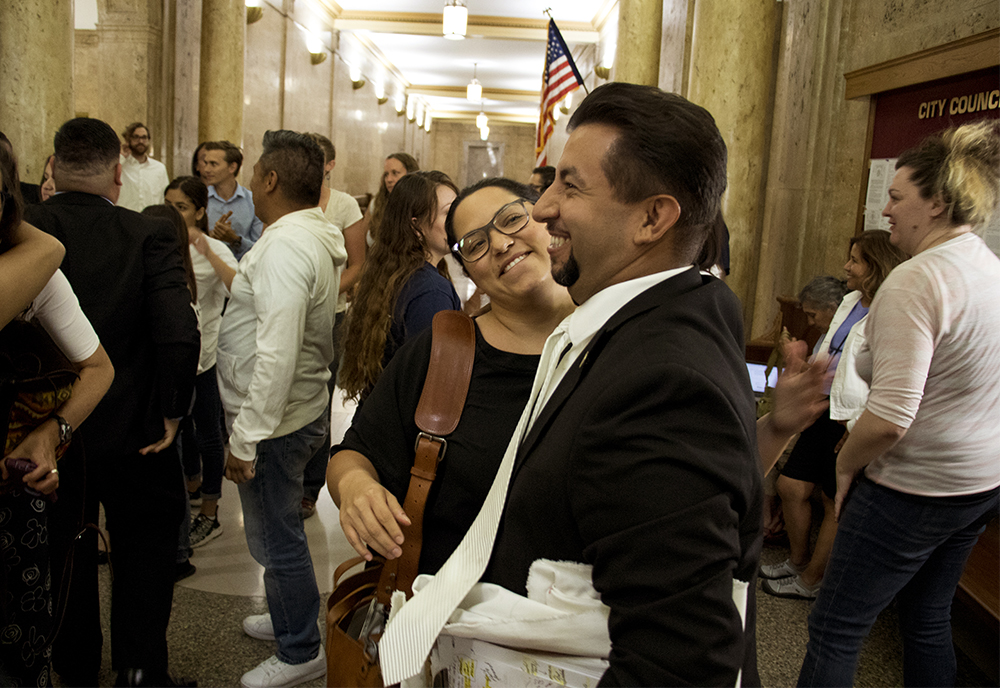 "Denver City Councilman Paul Lopez hugs Meyer Law Office Policy Director Julie Gonzales after a hearing on the ""Public Safety Enforcement Priorities"" ordinance, Aug. 28, 2017. (Kevin J. Beaty/Denverite)  denver; city council; politics; sanctuary city; denverite; kevinjbeaty; colorado; city and county building;"