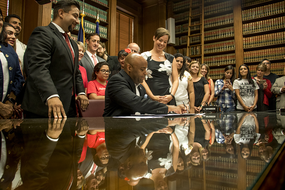 Mayor Michael Hancock signs an executive order on immigration policy, Aug. 31, 2017. (Kevin J. Beaty/Denverite)  immigration; sanctuary city; denver; colorado; denverite; city and county building; kevinjbeaty;