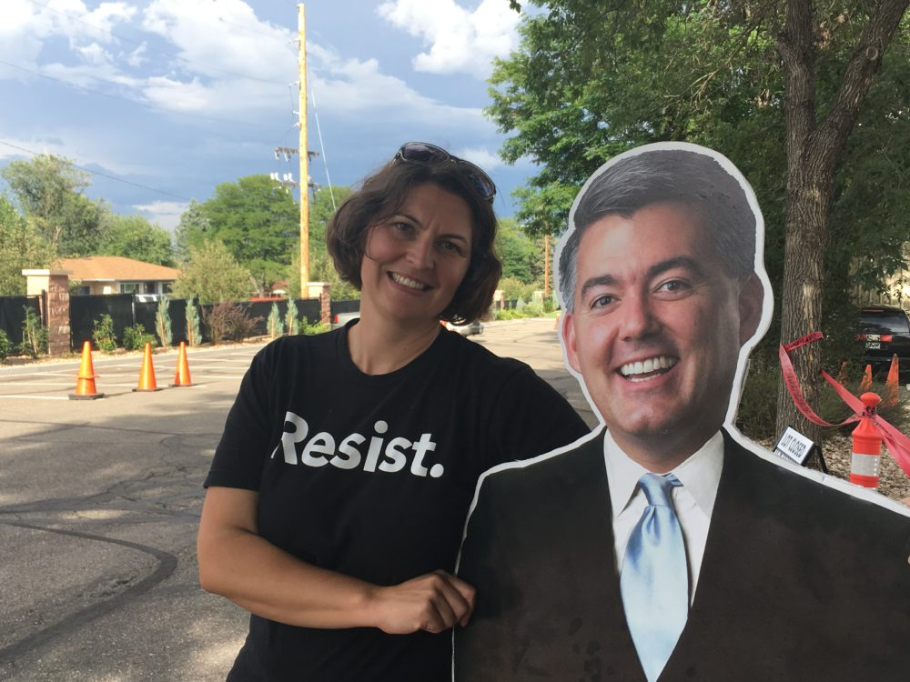 """Kristen Seidel of Indivisible Denver couldn't bring Cardboard Cutout Cory Gardner inside the town hall because he violated the """"no signs bigger than a sheet of paper"""" rule. Aug 15, 2017. (Erica Meltzer/Denverite)"""