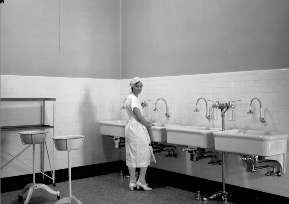 A surgical nurse stands near a row of large porcelain sinks in the scrub room at Denver General Hospital in Denver in 1931. (Western History & Genealogy Dept./Denver Public Library/X-28594)