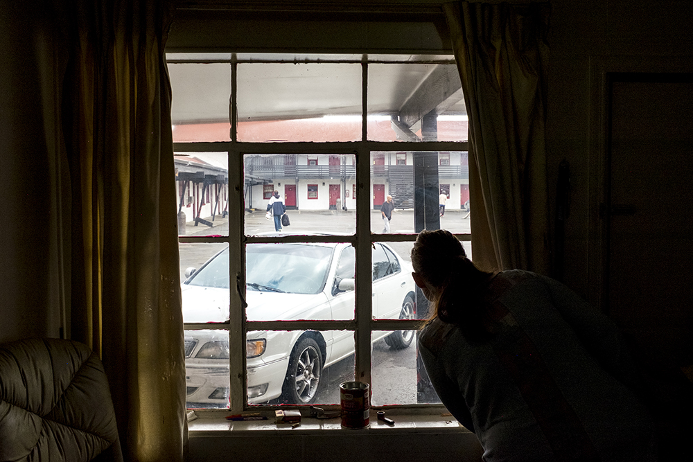 Ashley Angel peers out into the Carriage Motor Inn parking lot, where they've been living for two and a half months, Sept. 27, 2017. (Kevin J. Beaty/Denverite)  denver; colorado; denverite; kevinjbeaty; motel; colfax; affordable housing;
