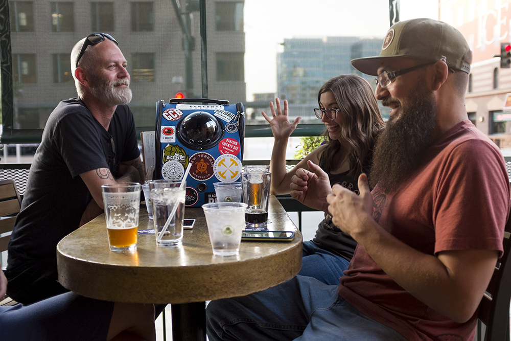 Elaia the brewery cat visits Wynkoop brewery with her owners, Michael Roberts (right to left) Myriah Robinson, and Wynkoop head brewer John Sims Aug. 30, 2017. (Kevin J. Beaty/Denverite)