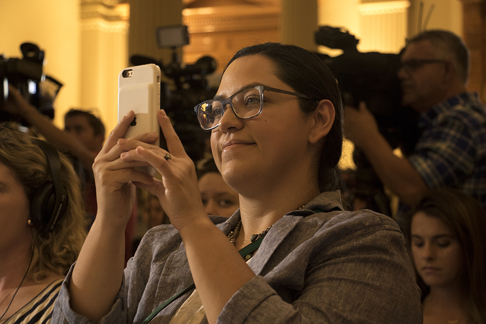 Julie Gonzales shoots video of a press conference on the possible repeal of Deferred Action for Childhood Arrivals, known as DACA, Sept. 1, 2017. (Kevin J. Beaty/Denverite)