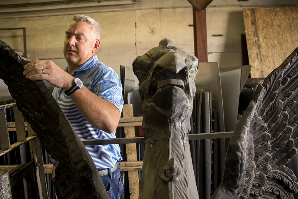 Scherer Metals Inc. co-owner Peter Bolan with an old Arapahoe Courthouse griffin inside his shop on Larimer Street, Sept. 6, 2017. (Kevin J. Beaty/Denverite)  griffin; sculpture; public art; kevinjbeaty; denverite; colorado; denver; five points; rino;
