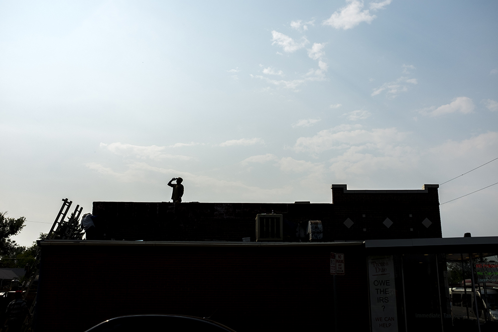 A man stands atop a roof on East Colfax Avenue near Fairfax Street, Sept. 7. 2017. (Kevin J. Beaty/Denverite)  denver; colorado; denverite; colfax; kevinjbeaty;