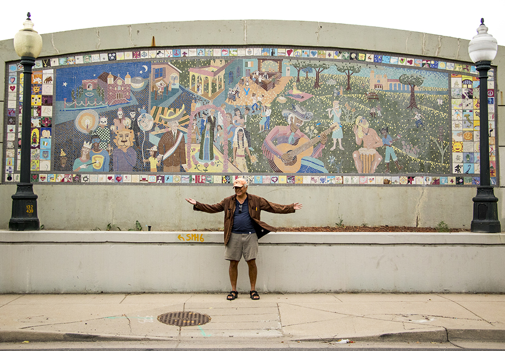 """Artist Bob Luna stands in front of """"Celebrations of the Neighborhood,"""" a mosiac that he and and Martha Keating installed on Kalamath Street in 1993, Sept. 11, 2017. (Kevin J. Beaty/Denverite)  kevinjbeaty; denver; denverite; colorado; highland; mural; public art;"""