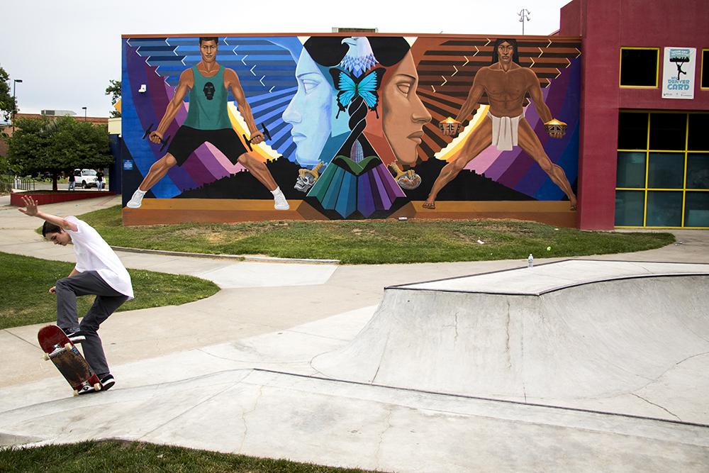Ryan Langley skates before the La Alma Murals by Emanuel Martinez at the La Alma Recreation Center, 11th Avenue and Osage Street. Sept. 11, 2017. (Kevin J. Beaty/Denverite)