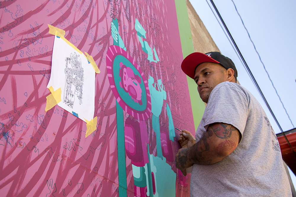 Santiago Jaramillo works on a mural behind La Casita on Morrison Road in Westwood, Sept. 11, 2017. (Kevin J. Beaty/Denverite)