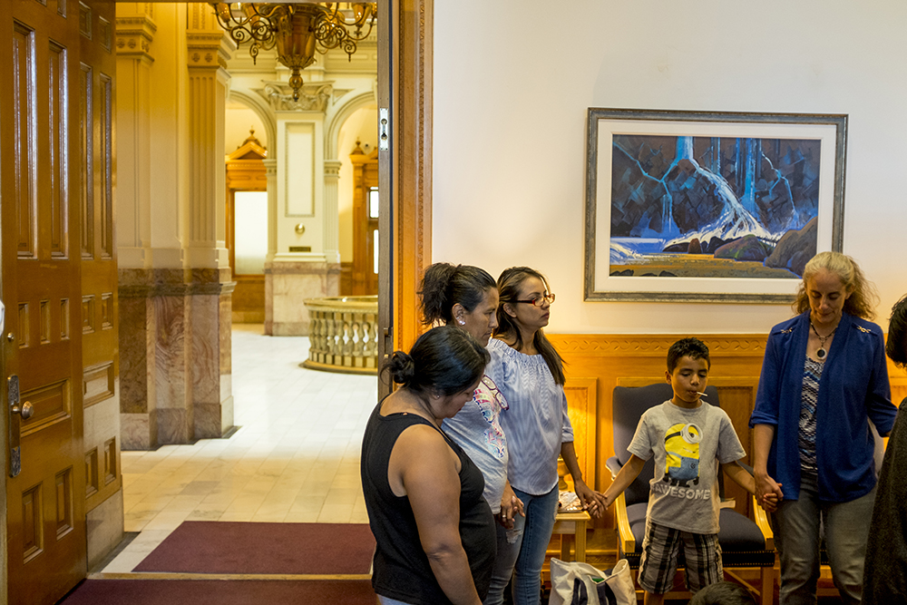 Ingrid Encalada prays with supporters in Governor Hickenlooper's office as they wait to see if he will pardon her felony identity theft charge, Sept. 13, 2017. (Kevin J. Beaty/Denverite)