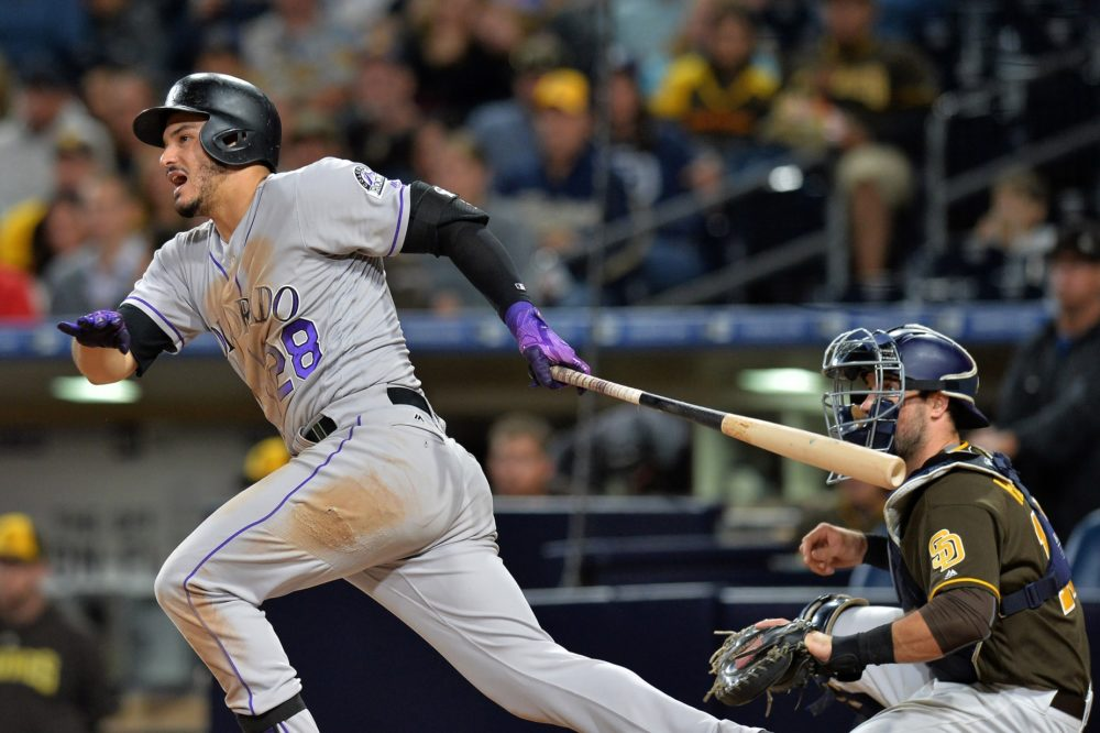 Colorado Rockies third baseman Nolan Arenado (28) singles during the eighth inning in front of San Diego Padres catcher Austin Hedges (right) at Petco Park. Sep 22, 2017; San Diego, CA. (Jake Roth/USA TODAY Sports)