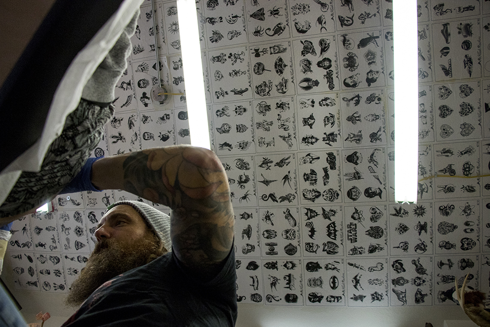 Tattoo artist Ryan Willard at work inside Marion Street Tattoo on East Colfax Avenue. (Kevin J. Beaty/Denverite)