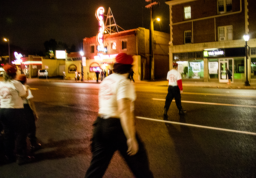 The Colorado Guardian Angels rush across Colfax Avenue as men begin yelling at each other in front of the Satire Lounge. Sept. 16, 2017. (Kevin J. Beaty/Denverite)  denver; colorado; guardian angels; capitol hill; denverite; colfax; kevinjbeaty;