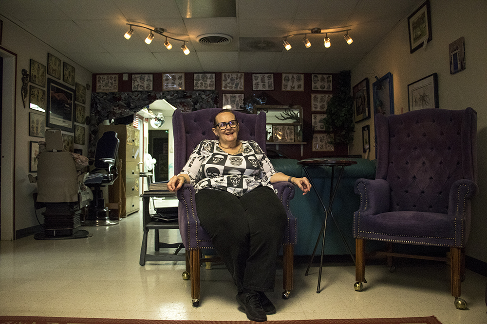 """The Blue Door tattoo parlor owner Beth Lovold, AKA """"Sister Bear,"""" in her shop on South Broadway. (Kevin J. Beaty/Denverite)  tattoo parlor; south broadway; kevinjbeaty; denver; colorado; denverite;"""