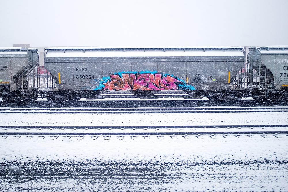 A train and some illicit art on a snowy day, Oct. 9, 2017. (Kevin J. Beaty/Denverite)