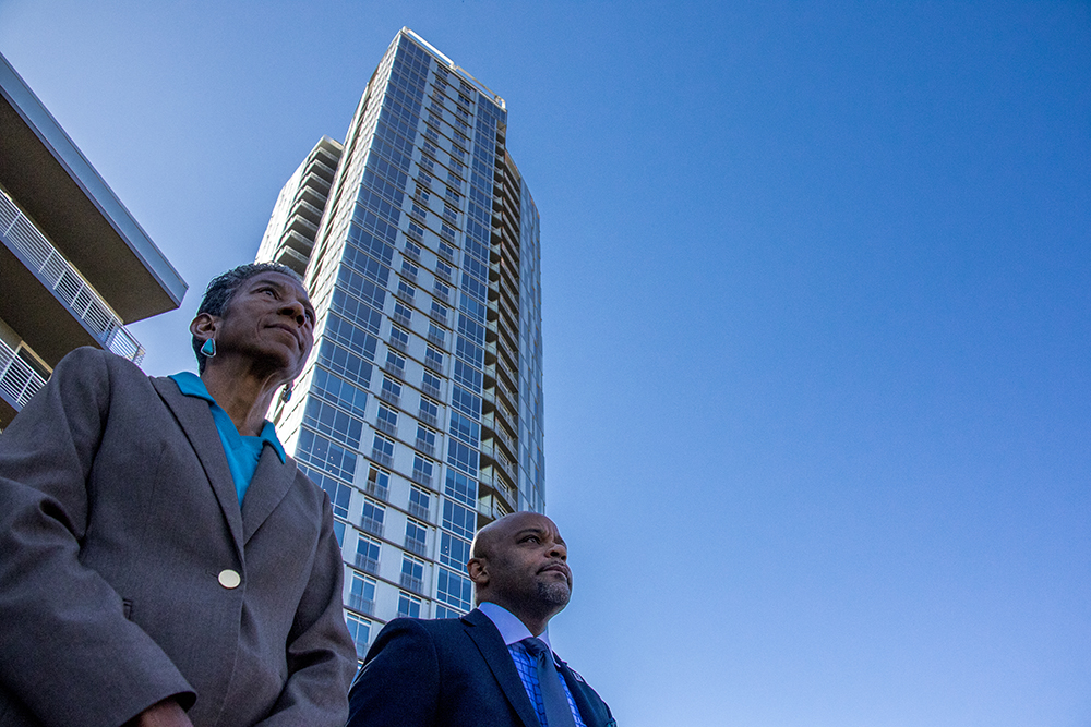 """Denver Parks & Recreation manager Allegra """"Happy"""" Haynes and Mayor Michael Hancock stand beneath The Confluence apartment tower while a press conference announced the near-end of Shoemaker Plaza's construction at Confluence Park, Oct. 12, 2017. (Kevin J. Beaty/Denverite)  confluence park; development; denver; colorado; kevinjbeaty; denverite; shoemaker plaza;"""