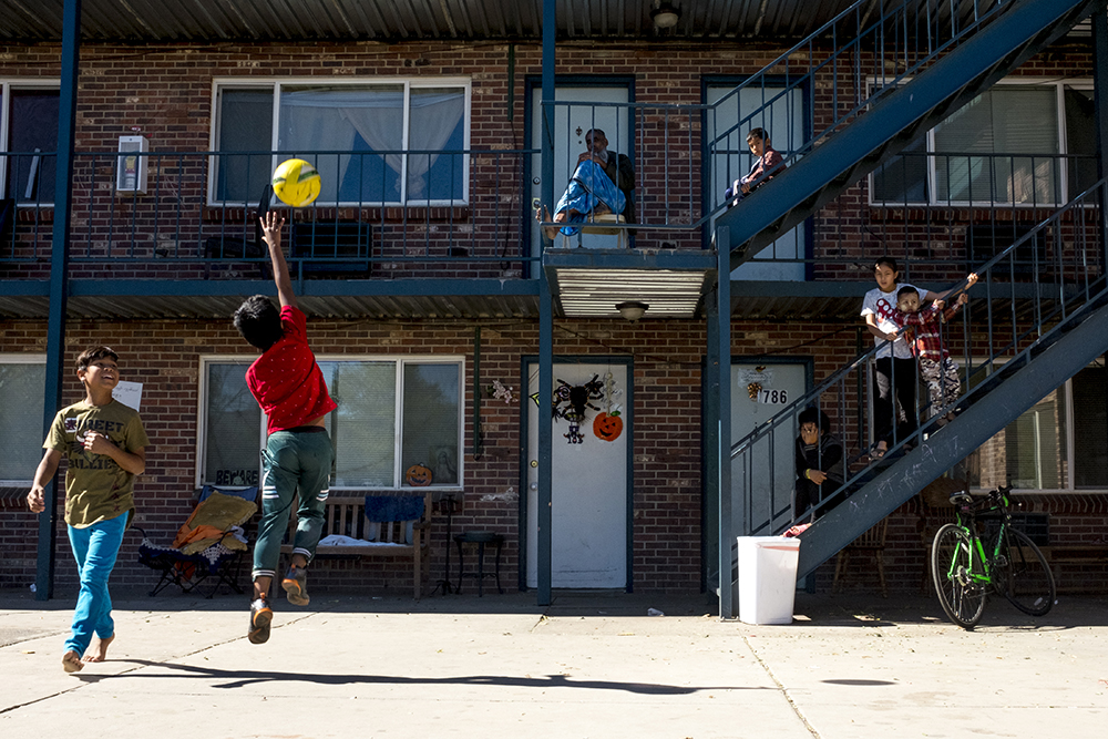 Kids play some variant of four square in the courtyard of an Aurora apartment building that's home to many of Denver's Burmese refugees, Oct. 15, 2017. (Kevin J. Beaty/Denverite)