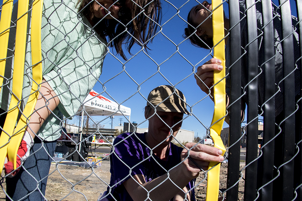 Jessica Weaber (left to right), Sage Primm and Rebecca Reil beautify a fence outside the Beloved Community Tiny Home Village, Oct. 29, 2017. (Kevin J. Beaty/Denverite)  tiny homes; beloved community tiny home village; rino; five points; homeless; right to rest; kevinjbeaty; denver; denverite; colorado;