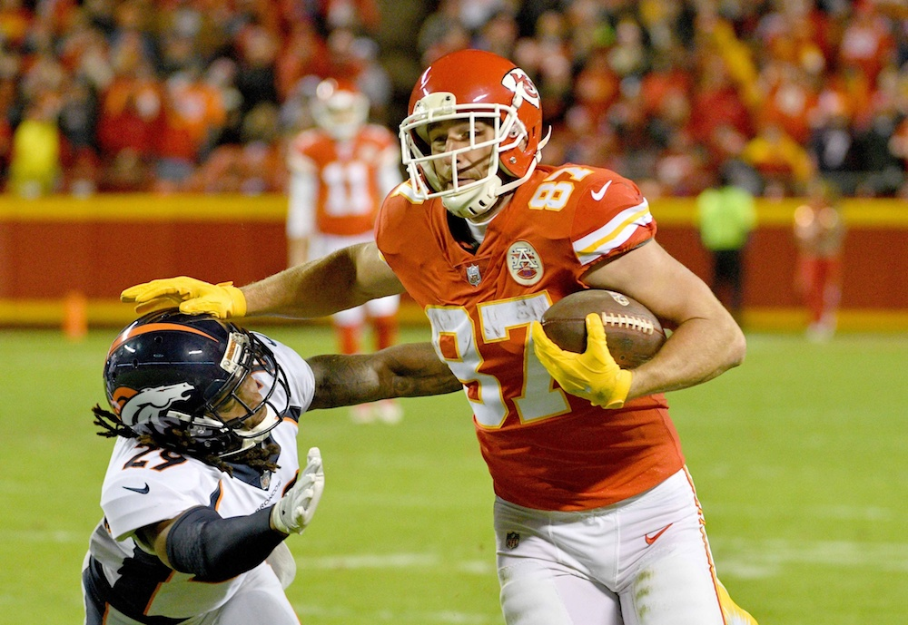 Travis Kelce stiff arms Bradley Roby. (Denny Medley/USA Today Sports)
