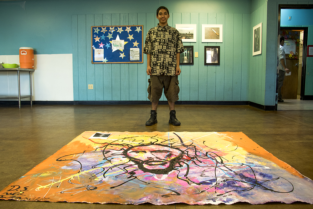 20-year-old Nicholas Jaramillo poses with a painting of Bob Marley that he made with an art volunteer at the Urban Peak youth homeless shelter in Overland, Nov. 2, 2017. (Kevin J. Beaty/Denverite)  homelessness; urban peak; acoma; homeless shelter; youth shelter; kevinjbeaty; denver; denverite; colorado;