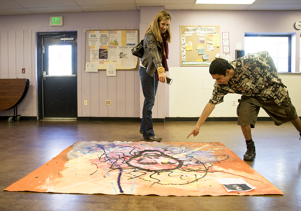 20-year-old Michael Jaramillo shows Urban Peak's CEO Christina Carlson the painting he made with an outreach volunteer, Nov. 2, 2017. (Kevin J. Beaty/Denverite)  homelessness; urban peak; acoma; homeless shelter; youth shelter; kevinjbeaty; denver; denverite; colorado;