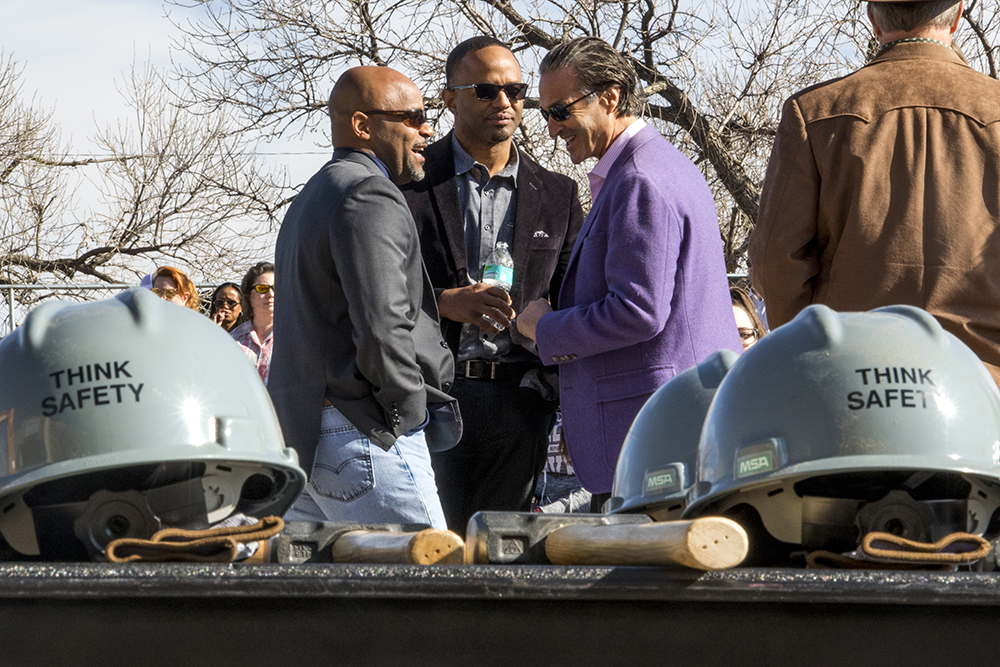 Mayor Michael Hancock (left to right), City Council President Albus Brooks and National Western Center real estate director Jeff Steinberg chat before the ceremony. Groundbreaking for the National Western Center at the old International Paper building in Elyria Swansea, Nov. 3, 2017. (Kevin J. Beaty/Denverite)denver; colorado; denverite; kevinjbeaty; national western center; development; elyria swansea; construction;