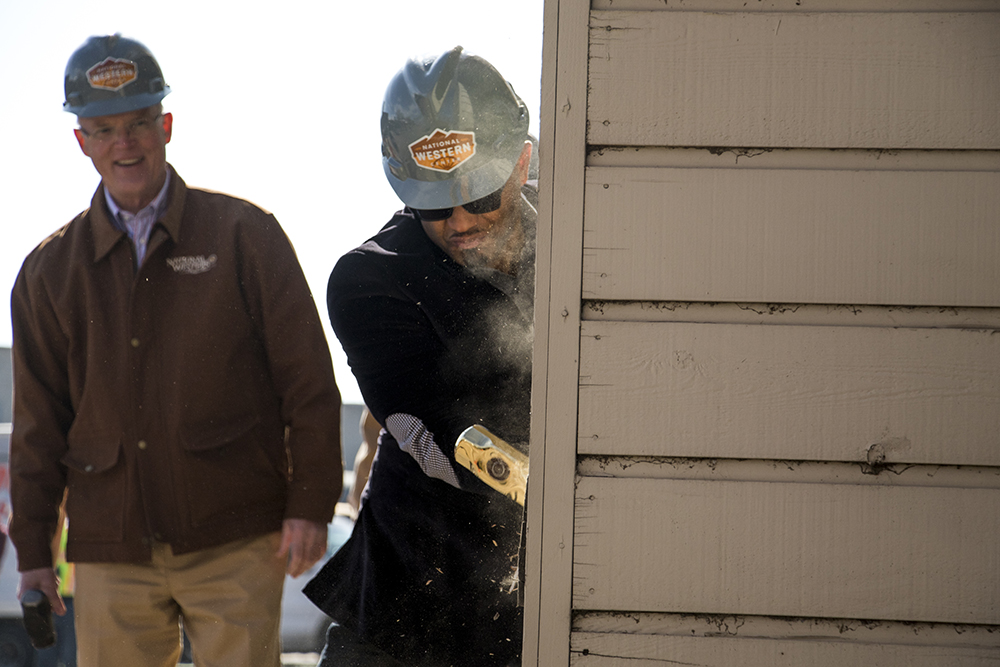 City Council President Albus Brooks takes a sledge hammer to the old International Paper building. Groundbreaking for the National Western Center in Elyria Swansea, Nov. 3, 2017. (Kevin J. Beaty/Denverite)  denver; colorado; denverite; kevinjbeaty; national western center; development; elyria swansea; construction;