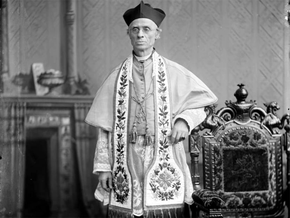 Portrait of the Right Reverend Joseph P. Machebeuf in an interior room next to a decorative carved chair with embroidered cushions, circa 1880. (Thomas Michael McKee/Denver Public Library/Western History Collection/Z-1478)  catholic; religion;