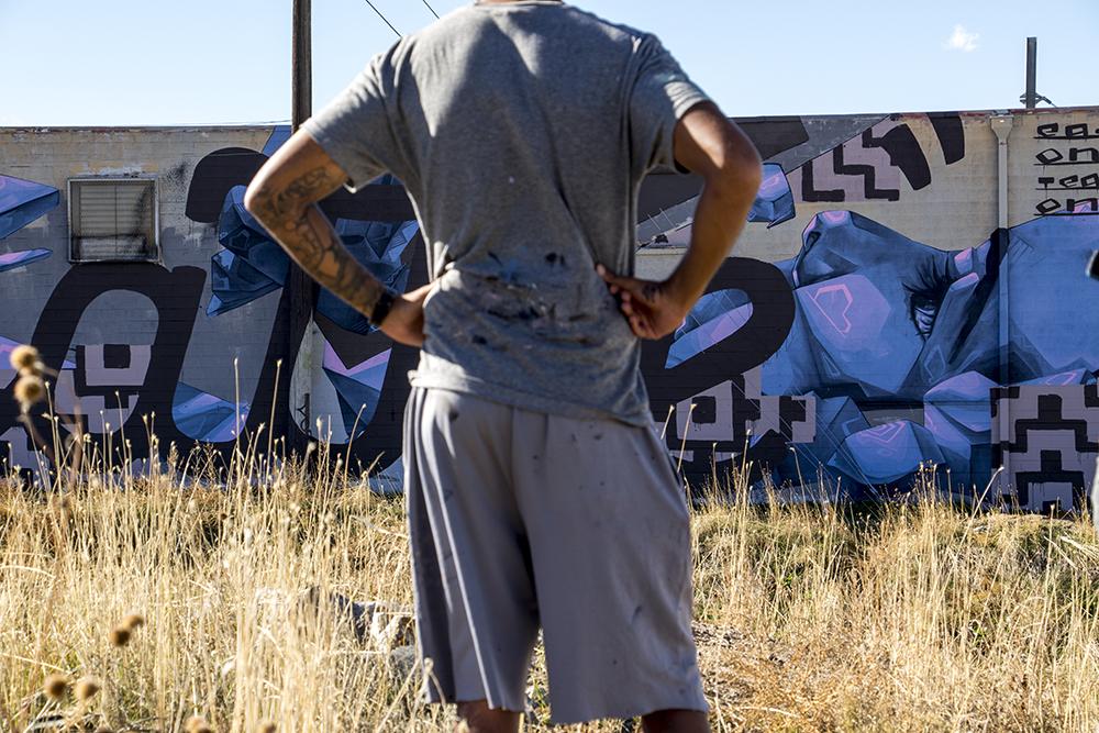 Artist Belove near one of his largest murals, Elyria Swansea, Nov. 13, 2017. (Kevin J. Beaty/Denverite)  denver; colorado; denverite; kevinjbeaty; elyria swansea; graffiti; belove;