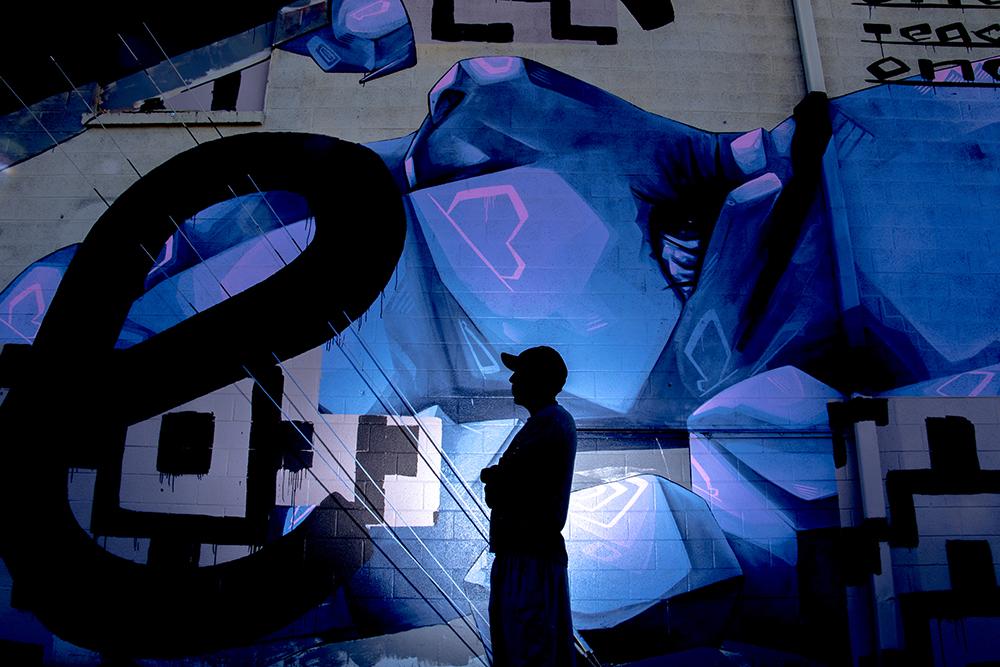 Artist Belove poses for a portrait near one of his largest murals, Elyria Swansea, Nov. 13, 2017. (Kevin J. Beaty/Denverite)  denver; colorado; denverite; kevinjbeaty; elyria swansea; graffiti; belove;
