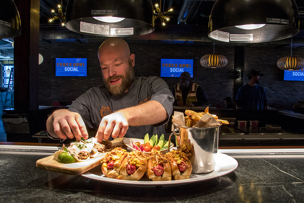 Regional Executive Chef Caleb Benton puts the final touches on a Dawgy Style platter. Punch Bowl Social Stapleton days before its grand opening, Nov. 15, 2017. (Kevin J. Beaty/Denverite)  denver; colorado; denverite; kevinjbeaty; punch bowl social; stapleton; food; restaurant; nightlife; bar;