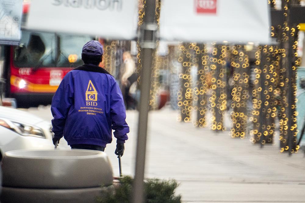 A member of the Downtown Denver BID's Clean Team at work on the 16th Street Mall, Nov. 29, 2017. (Kevin J. Beaty/Denverite)  16th street mall; denver; colorado; central business district; denverite; kevinjbeaty; purple shirt; downtown denver partnership;