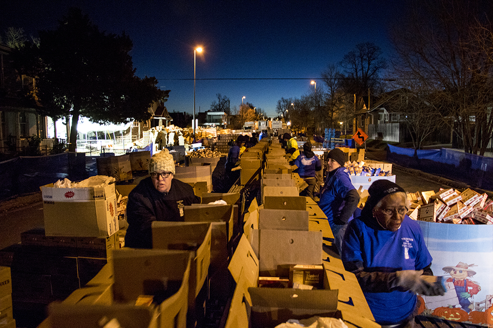 Dawn breaks over the assembly line. The Epworth Foundation's annual Feed a Family Thanksgiving dinner giveaway, Nov. 18, 2017. (Kevin J. Beaty/Denverite)  denver; colorado; denverite; kevinjbeaty; cole; thanksgiving; food pantry; food insecurity;