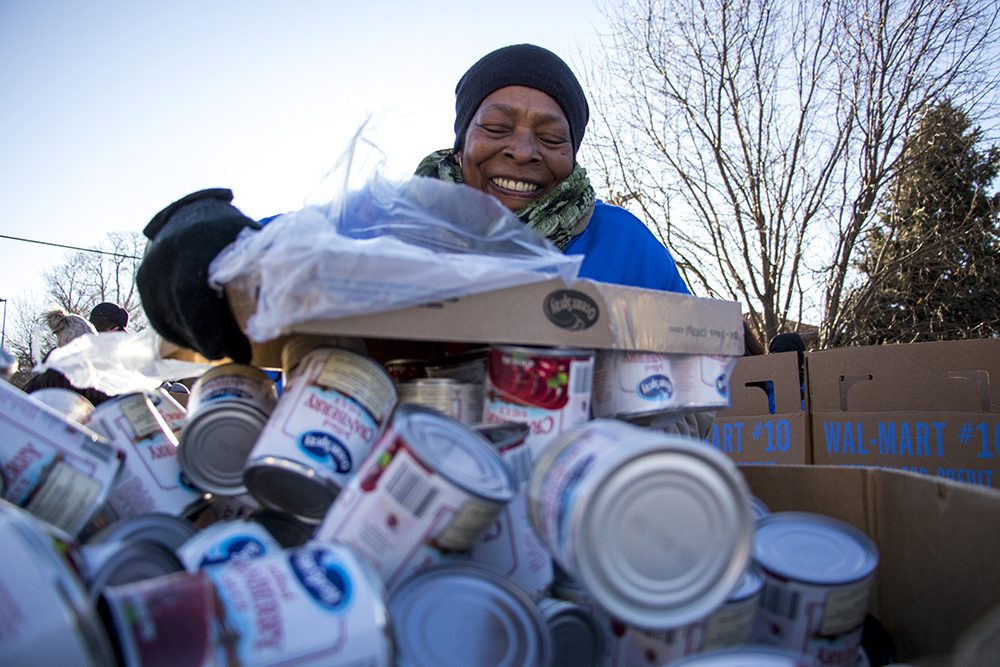 Darlene Wedgeworth dumps canned vegetables into a staging box. The Epworth Foundation's annual Feed a Family Thanksgiving dinner giveaway, Nov. 18, 2017. (Kevin J. Beaty/Denverite)  denver; colorado; denverite; kevinjbeaty; cole; thanksgiving; food pantry; food insecurity;