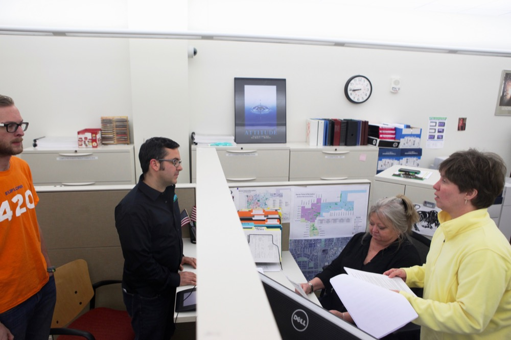 Bobby Reginelli of Euflora, center, learns from city staffers Erin Burke and Kris Ryan that he will not be granted the permit to host 4/20 in Civic Center Park. (Andrew Kenney/Denverite)