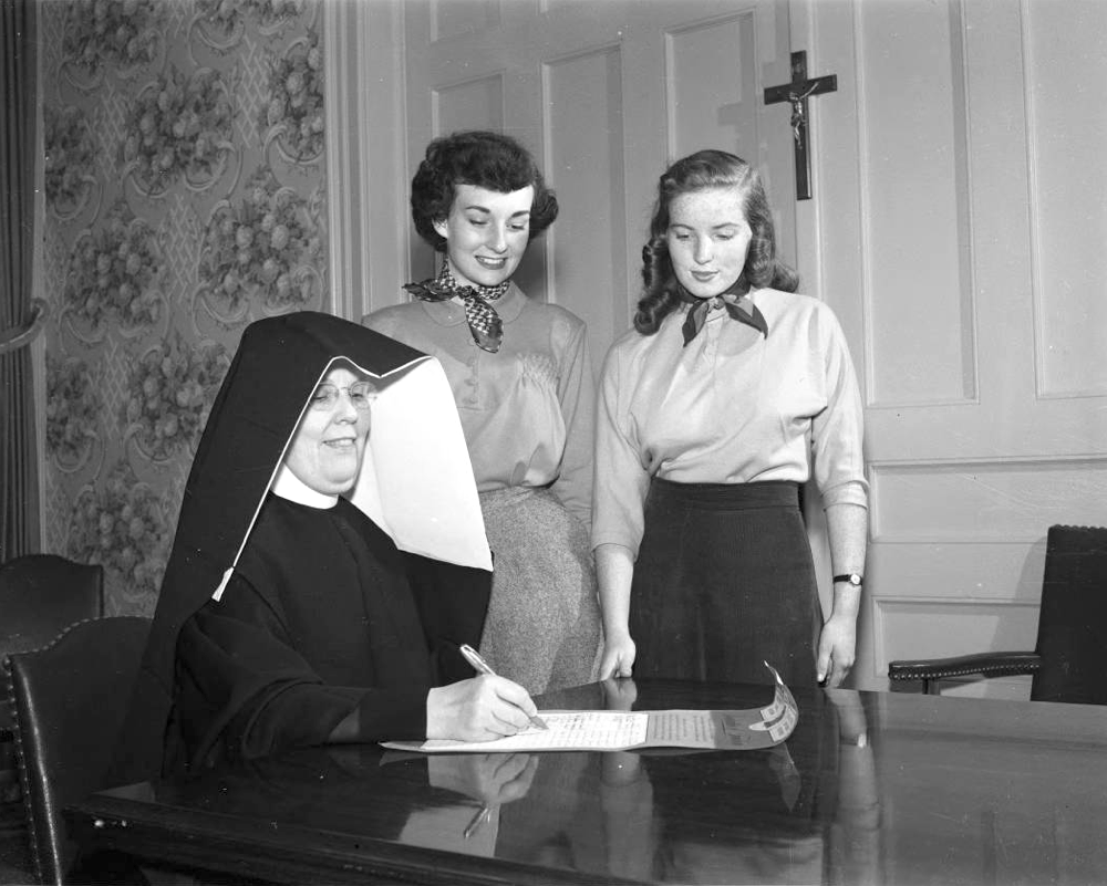 Women look on as a Sister of Loretto nun fills out a form at Loretto Heights College in Denver, Sept. 21, 1950. (Lloyd Rule, Denver Public Library Western History Collection, Z-10228)