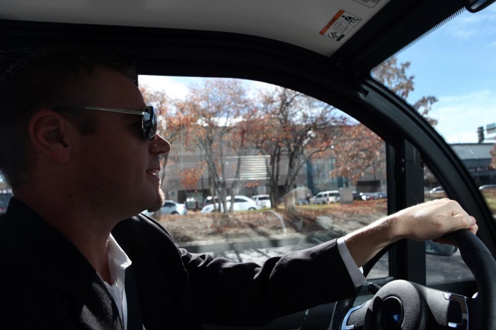 Mike Sweeny drives an electric vehicle through Cherry Creek. (Andrew Kenney/Denverite)