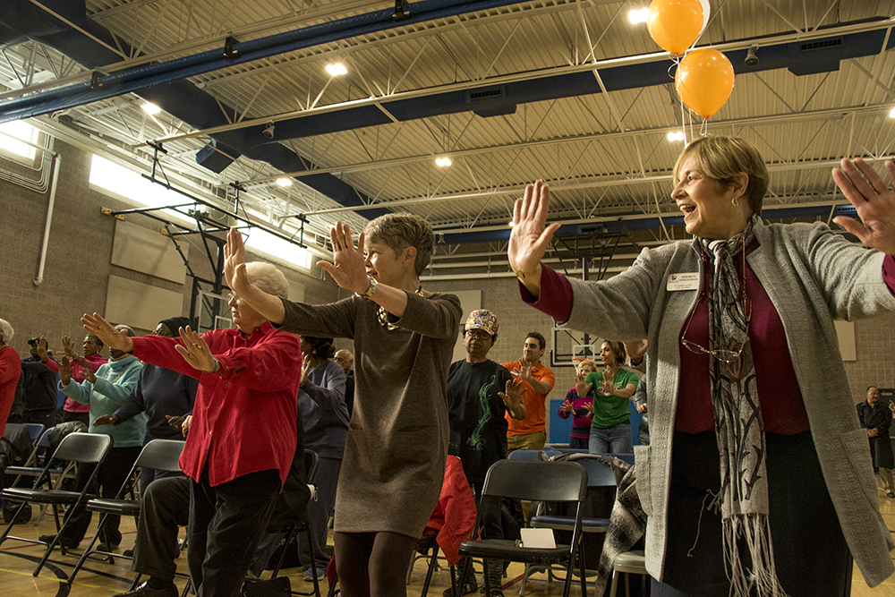 """Maureen Spiegleman (right), incoming chair of the Denver Commission on Aging, dances as part of a """"SilverSneakers"""" presentation during the press conference. Denver announces the inception of Denver Prime, free access to rec centers for Denver residents over 60. Dec. 6, 2017. (Kevin J. Beaty/Denverite)  denver; colorado; denverite; kevinjbeaty; rec center; aging; lowry field;"""