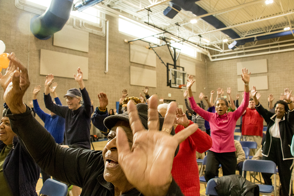 "86 year-old Mary Robinson dances during a ""SilverSneakers"" activity at the end of the program. A press conference announcing the inception of Denver Prime, free access to rec centers for Denver residents over 60. Dec. 6, 2017. (Kevin J. Beaty/Denverite)  denver; colorado; denverite; kevinjbeaty; rec center; aging; lowry field;"