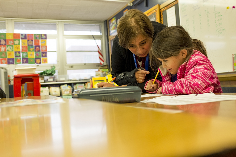Paraprofessional Bertha Finney works with a first grade student on a writing assignment at Goldrick Elementary School, Dec. 7, 2017. (Kevin J. Beaty/Denverite)