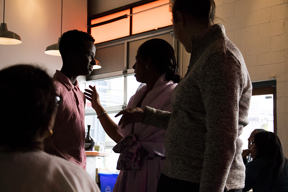 Sara Gebre speaks with her eldest son, Matthew. Ethiopian coffee service gets kicked off at Comal Kitchen, Dec. 14, 2017. (Kevin J. Beaty/Denverite)  denver; colorado; denverite; kevinjbeaty; comal kitchen; food; globeville; taxi;