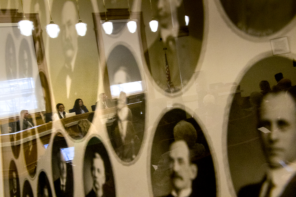 Speaker of the House Crisanta Duran and House majority leader K.C. Becker, seen reflected in a frame of portraits of an all-white-male Colorado Senate from another era, as they sit on a legislative executive committee meeting on sexual harassment at the Capitol, Dec. 15, 2017. (Kevin J. Beaty/Denverite)  government; copolitics; denver; colorado; denverite; legislation; sexual harassment; kevinjbeaty;