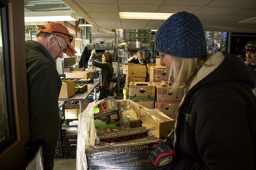 Dana Van Daele and Tim Sanborn load a palate of vegetables into the Metro Caring food pantry in City Park West. A ride-along with We Don't Waste, Dec. 18, 2017 (Kevin J. Beaty/Denverite)  denver; colorado; denverite; food insecurity; food; sustainability;