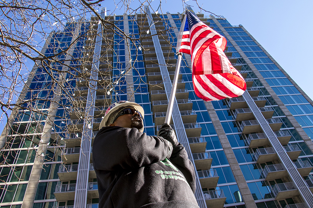 Emmett Cromwell holds an American flag beneath SkyHouse Denver during a news conference announcing that SkyHouse workers reached a settlement about wage law violations, Dec. 20, 2017. (Kevin J. Beaty/Denverite)  construction workers; wage theft; downtown; denver; colorado; denverite;