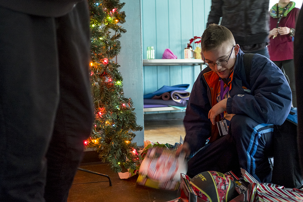 Chris F. eagerly opens gifts for everyone at the shelter. Christmas Day at Urban Peak, a shelter for Denver's homeless youth, Dec. 25, 2017. (Kevin J. Beaty/Denverite)  homeless; urban peak; denver; denverite; colorado; kevinjbeaty;