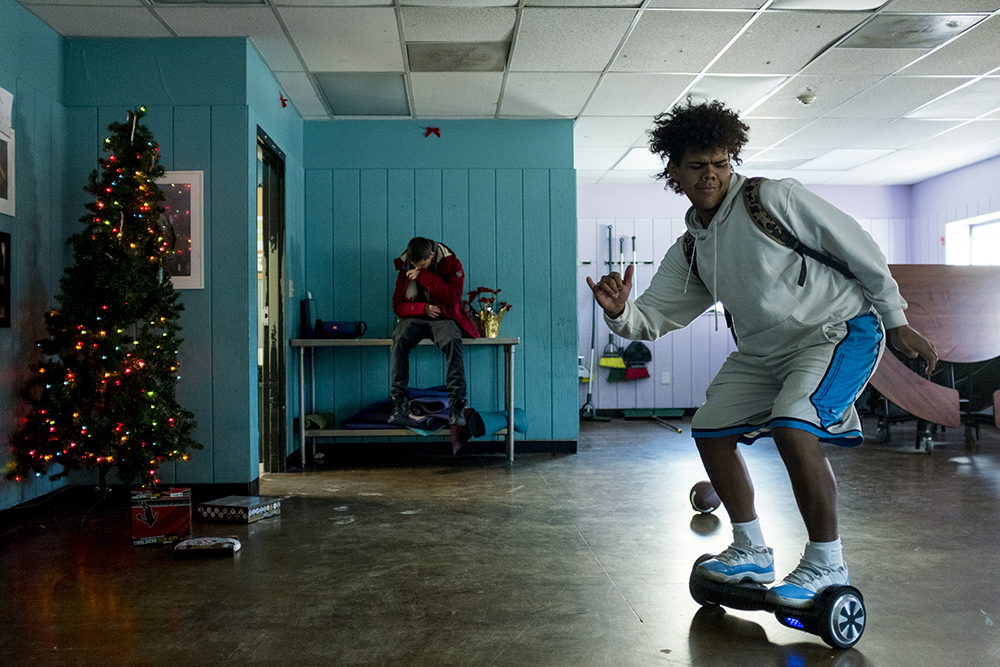 "Garret, who's 18 and has only been here for two weeks, dances on a ""hoverboard."" Christmas Day at Urban Peak, a shelter for Denver's homeless youth, Dec. 25, 2017. (Kevin J. Beaty/Denverite)  homeless; urban peak; denver; denverite; colorado; kevinjbeaty;"