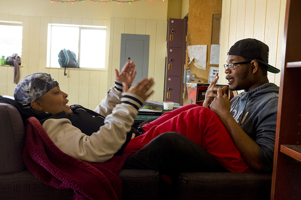Zee, 19, and her husband Chris S., 20, who are both deaf, sign to each other as they cuddle. Christmas Day at Urban Peak, a shelter for Denver's homeless youth, Dec. 25, 2017. (Kevin J. Beaty/Denverite)  homeless; urban peak; denver; denverite; colorado; kevinjbeaty;