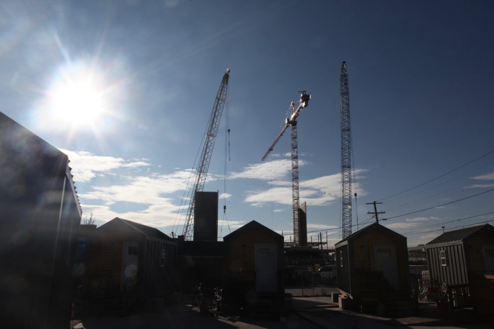 """The """"tiny homes"""" of the Beloved Community Village beneath towering construction cranes in River North. (Andrew Kenney/Denverite)"""