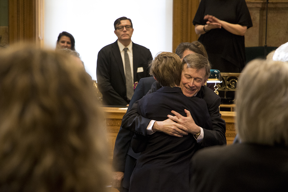 Governor John Hickenlooper hugs his son, Teddy, after making his State of the State address, Jan. 11, 2017. (Kevin J. Beaty/Denverite)  copolitics; governor john hickenlooper; denver; colorado; denverite; kevinjbeaty;